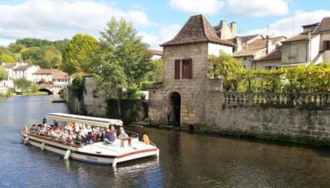 An open topped tourist boat full of tourists on the river at Brantome