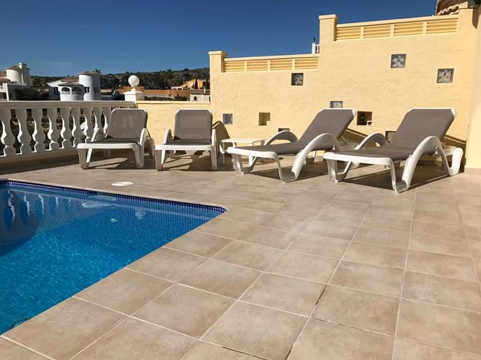 Four sun loungers on the pool terrace