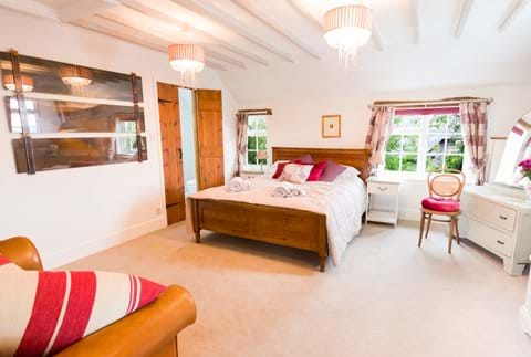 A large bedroom in a Devon holiday cottage with king-size bed and en suite bathroom